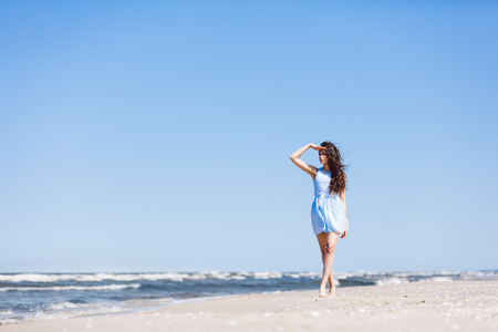 A young girl walking on the beach, looking steadily at the sea. Sunny vacations. Stock Photo