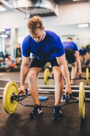 Fit man lifting weights at the gym. Sporty lifestyle and bodybuilding.