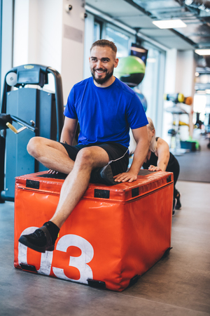 Happy man sitting on weight pushed by a woman. Gym exercises. Sport and physical activity.