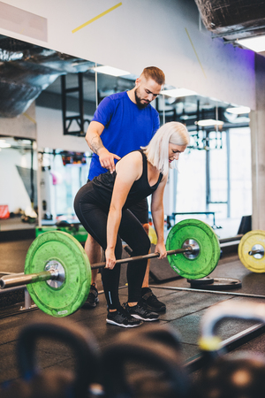 Personal trainer assisting woman lifting weights. Fitness club. Sporty lifestyle.