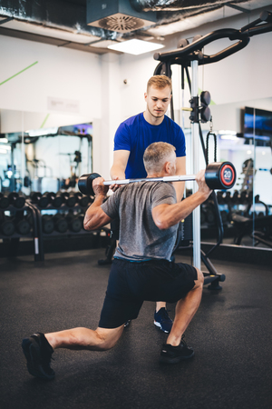 Senior man exercising with personal trainer. Sporty lifestyle on retirement.