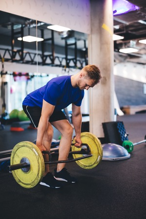 Muscular man lifting weights at the gym. Strong body, exercising and sport.