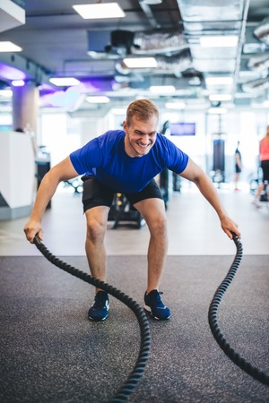 Young man exercising with ropes at the gym. Healthy sportive lifestyle.