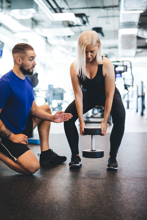 Gym trainer assisting the exercising woman. Shaping the body. Personal training.