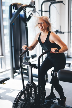Young woman riding on an air bike at the gym. Spinning, cycling indoors.