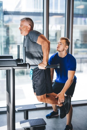 Young man helping senior man with his workout at a gym. Personal trainer. Active retirement. Stock Photo