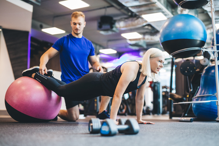 Woman working out on a ball with personal trainer. Gym instructor. Exercising.