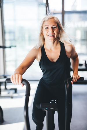 Happy woman riding a bicycle at the gym. Indoor workout. Physical activity. Stock Photo