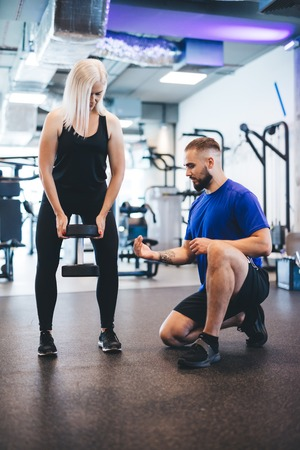 Woman exercising with personal trainer. Weightlifting. Sporty lifestyle.