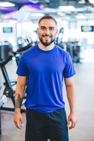 Happy man standing in a gym. Fit lifestyle. Active people.