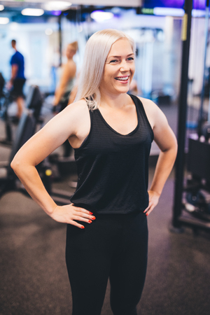 Smiling woman standing in a gym, looking aside. Personal trainer. Fit lifestyle.