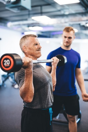 Senior man weightlifting, assisted by personal trainer. Retirement activities. Fit lifestyle.