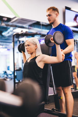 Woman at the gym exercising with personal trainer. Active lifestyle. Workout.
