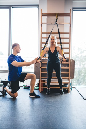 Young man assisting an exercising woman. Personal trainer, gym instructor. Sport.