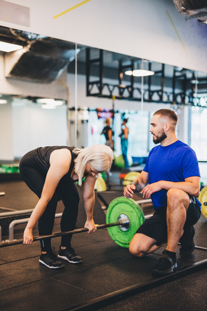 Personal trainer assisting woman lifting weights. Working out and getting in shape. Stock Photo
