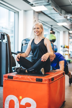 Happy woman sitting on weight pushed by a man. Gym exercises. Sport and physical activity. Stock Photo