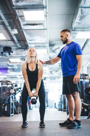 Woman working out with personal trainer at a gym. Fitness instructor. Stock Photo
