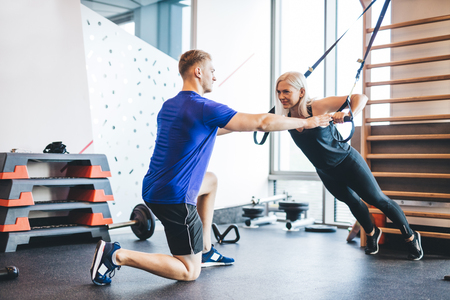 Woman exercising with personal trainer at the gym. Bodybuilding and working out.