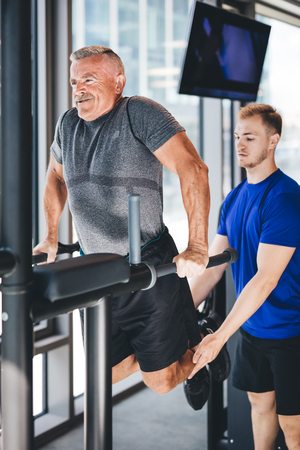 Gym instructor helping senior man at the gym. Sport and physical training. Stock Photo