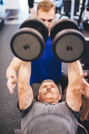 Senior man lifting weights assisted by gym instructor. Bodybuilding. Fit lifestyle. Stock Photo