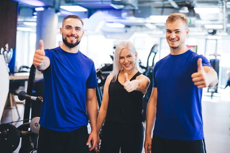 Three happy people at the gym showing thumbs up. Approval and success. OK gesture.