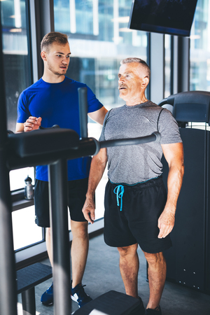 Personal trainer giving instructions to older man at the gym. Physical activity of senior people. Stock Photo