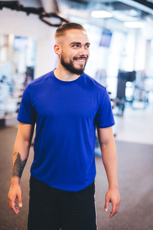 Smiling man standing in a gym, looking aside. Personal trainer, fitness coach.