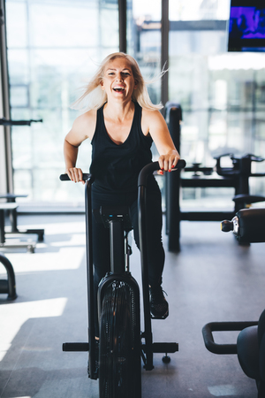 Happy woman riding an air bike at the gym. Working out indoors. Healthy activities.