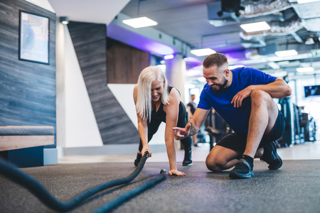 Gym instructor and a woman exercising at the gym. Sportive lifestyle, body shaping. Stock Photo