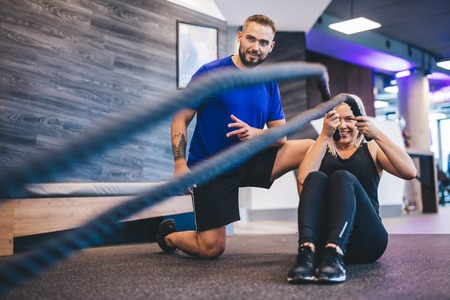 Young woman exercising with personal trainer at the gym. Workout with ropes. Sportive lifestyle.