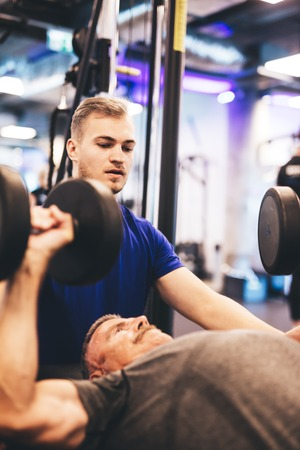 Personal trainer instructing older man during exercise. Gym activities. Weightlifting.