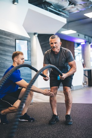 Senior man exercising with ropes at the gym. Personal training. Healthy lifestyle.