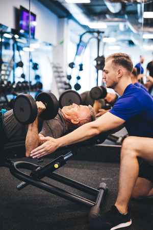 Young man assisting senior man at the gym. Personal trainer, retirement activities.