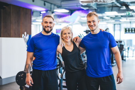 Three happy young people standing at the gym, hugging. Team and teamwork. Stock Photo