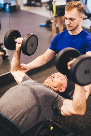 Personal trainer assisting older man in an exercise. Retirement activities. Health.