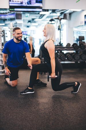 Woman exercising with personal trainer at the gym. Workout assistance. Healthy lifestyle.