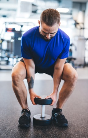 Young man lifting dumbbell at the gym. Bodybuilding and exercising. Strong body.