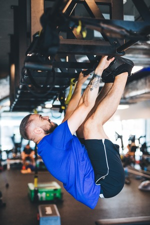 Man pulling his body up on the rig at the gym. Gymnastics and sport. Physical strength. Stock Photo