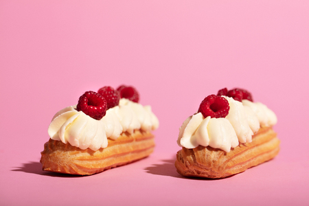Two colorful eclairs laying on pink background. French sweet dessert. Homemade pastry.