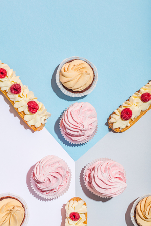Sweet cakes on pastel background in a composition. Delicious treat. Flat lay.