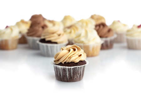 Frosted caramel cupcake in a close-up. Blurred muffins in the background. Sweet treat. Dessert.