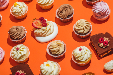 Colorful desserts laying on orange background. Delicious decorated pastry. Flat lay.