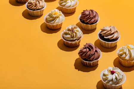 Delicous muffins standing in two rows on yellow background. Copyspace. Sweet cakes.