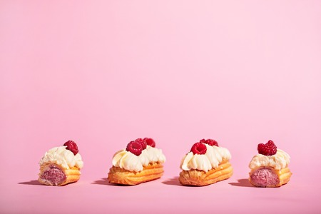 Four colorful eclairs with raspberries on pink background. Tasty sweet snack. French cuisine. Stock Photo