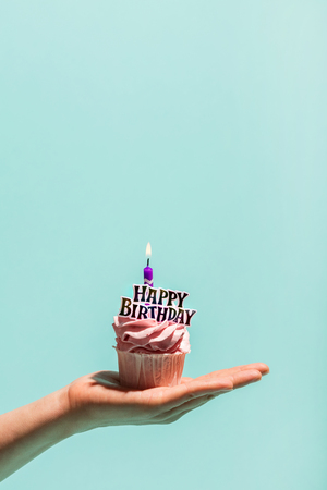 Womans hand holding birthday cupcake with candle. Happy birthday. Celebration. Stock Photo
