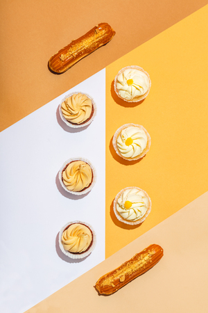 Flat lay composition of sweet desserts. Bright, warm colors. Cupcakes and eclairs, pastry.