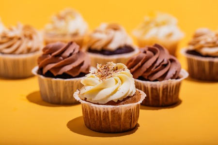 Vanilla muffin in a close-up on yellow background. Cupcakes. Sweet pastry. Stock Photo