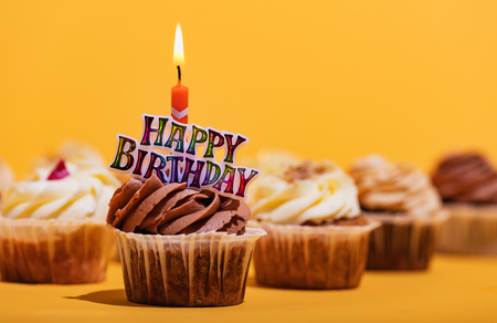 Decorated birthday muffin with candle on yellow background. Party and celebration. Sweet dessert. Stock Photo