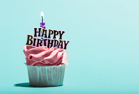 Birthday muffin with candle on a pastel blue background. Sweet treat. Celebration. Stock Photo
