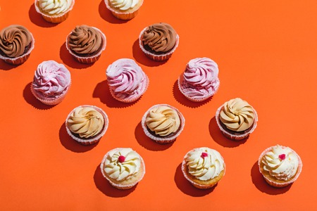 Colorful cupcakes in three rows on orange background. Sweet tasty desserts. Top view.